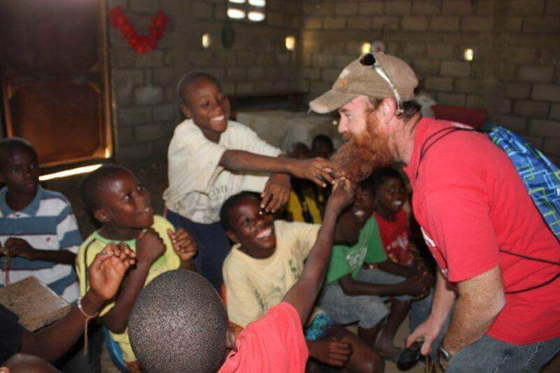 This is a typical scene in Haiti - kids playing with Tim's beard!