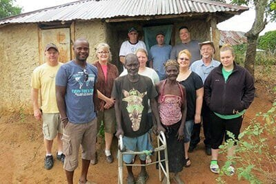 The whole team, in front of one of the families they prayed with and delivered food to.