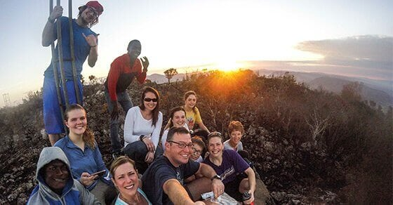A group of hikers take a selfie on the top of a plateau.