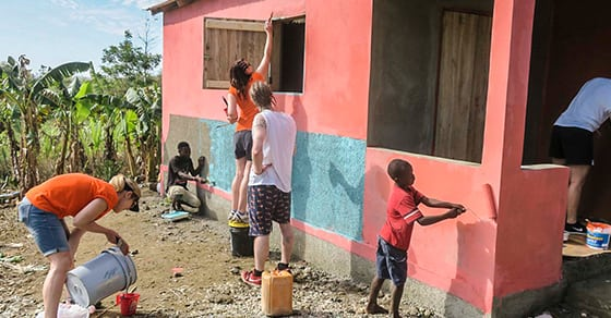 Volunteers paint the exterior of a new house.
