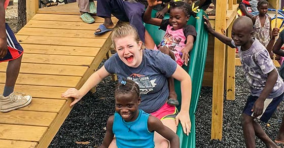 A volunteer goes down a slide with children.