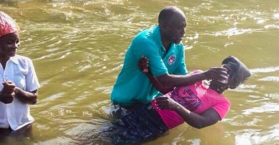 A Haitian man baptizes a Haitian woman in some water.