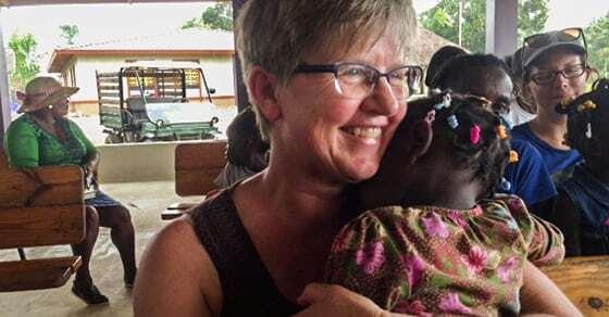 A woman hugs a small girl.