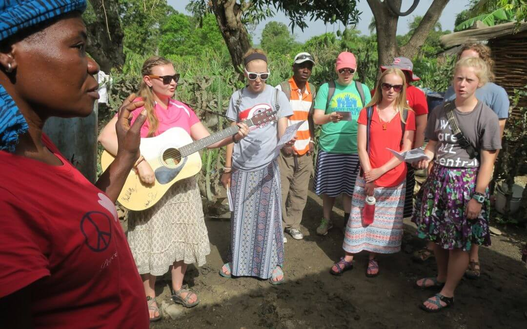 A team sings at a house belonging to a Haitian family.