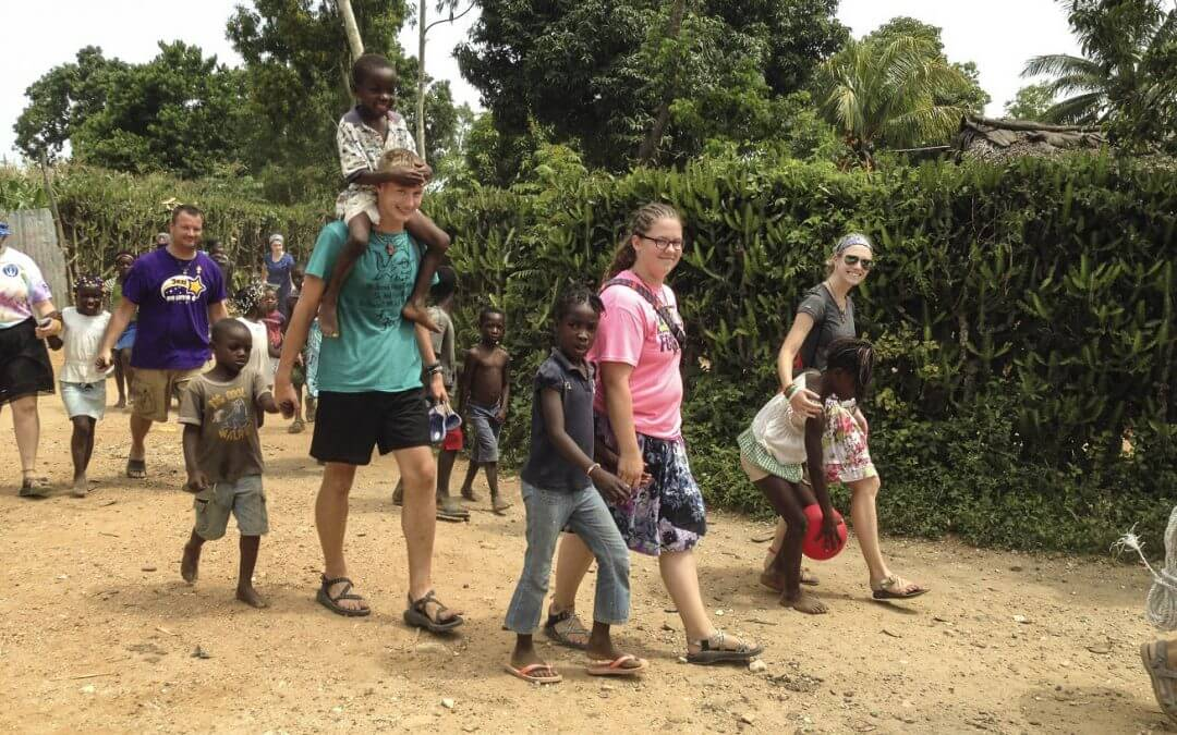 Volunteers and children walk along a path together.