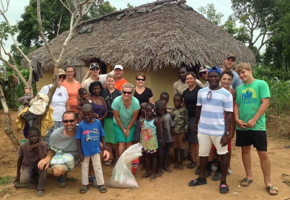 A team of volunteers and community members pose after delivering rice to a lady who gave up on being close to voodoo.