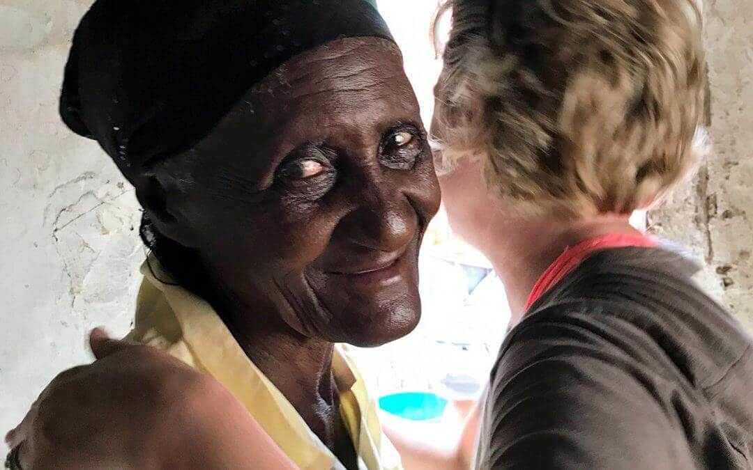 A volunteer and an elderly woman from the community embrace.