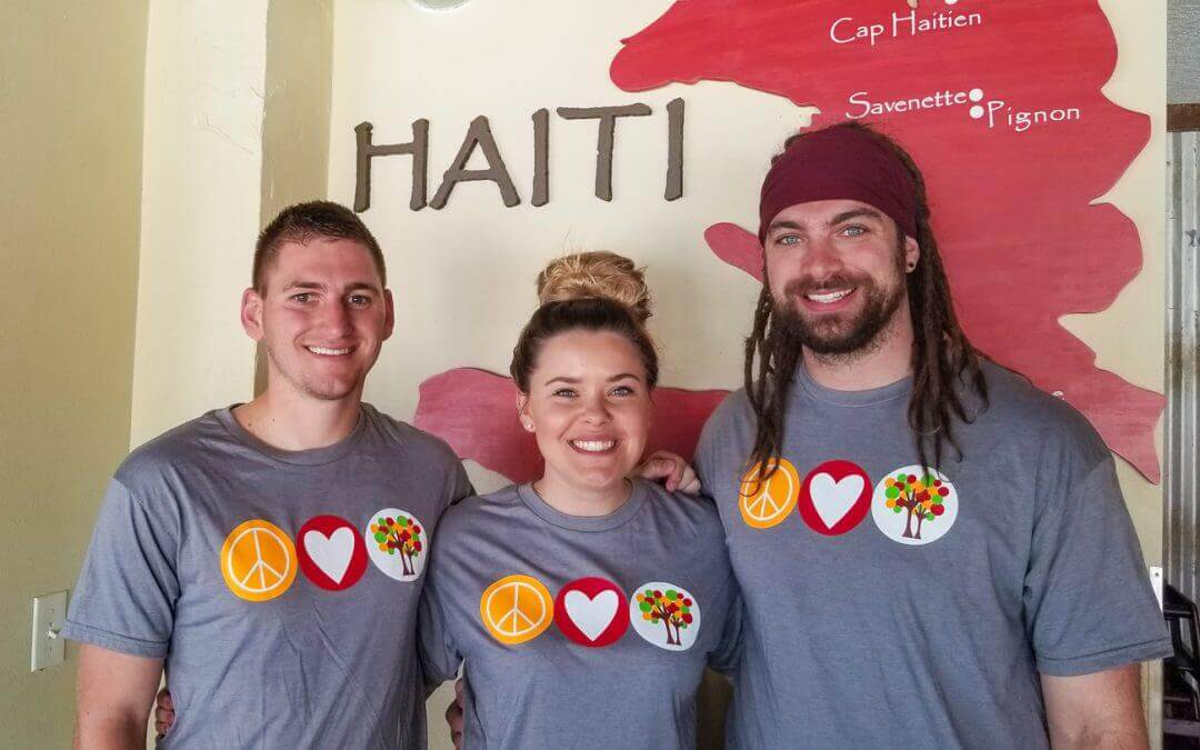Three workers smile in front of a Haiti mural.