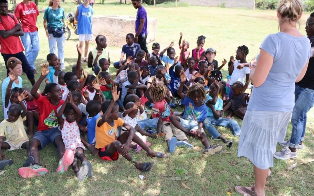 Children raise their hands at vacation bible school.