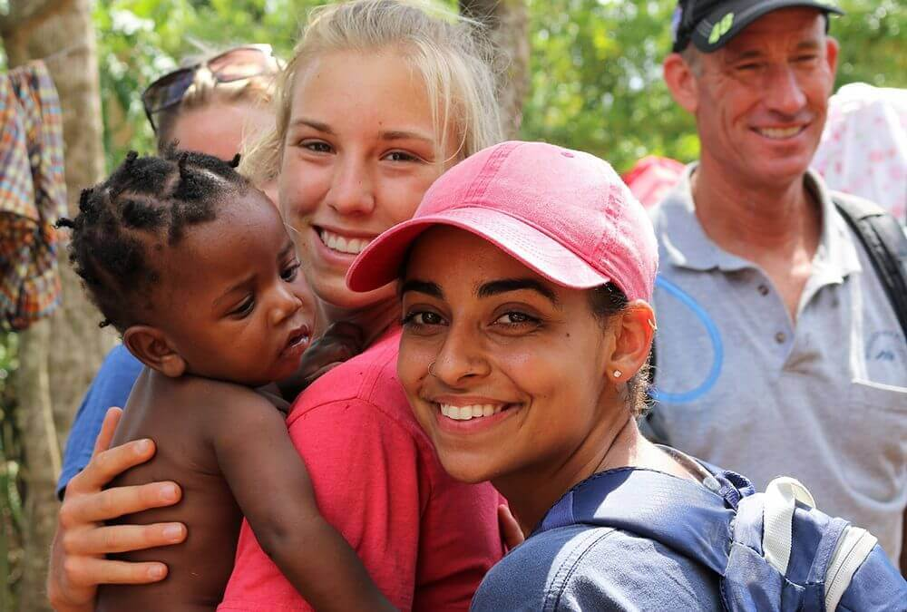 Volunteers smile with a baby in their arms.