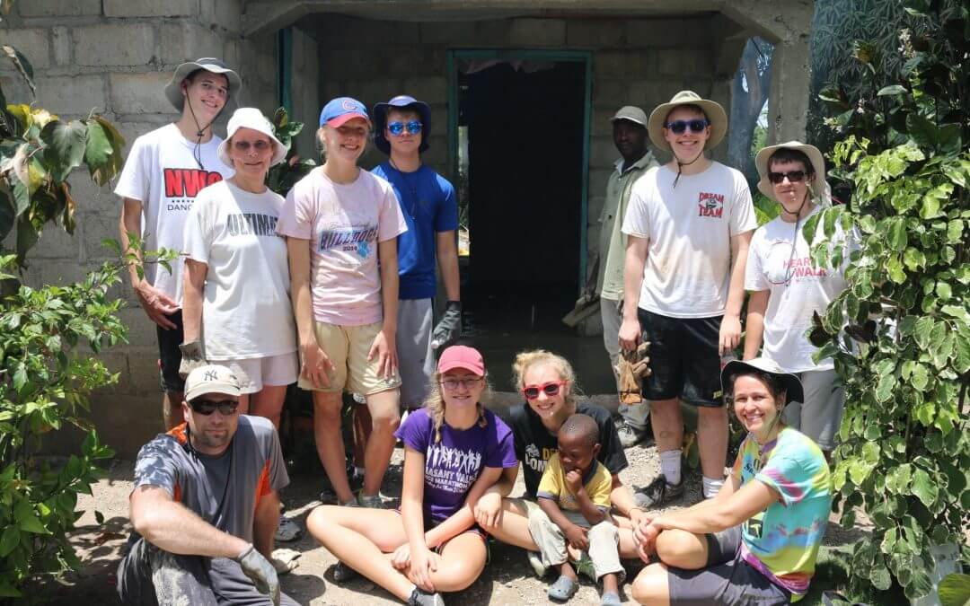 Volunteers pose outside of a stone building.