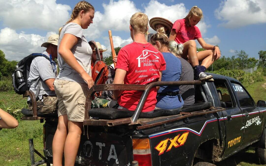 Volunteers sit on the back of a pickup.