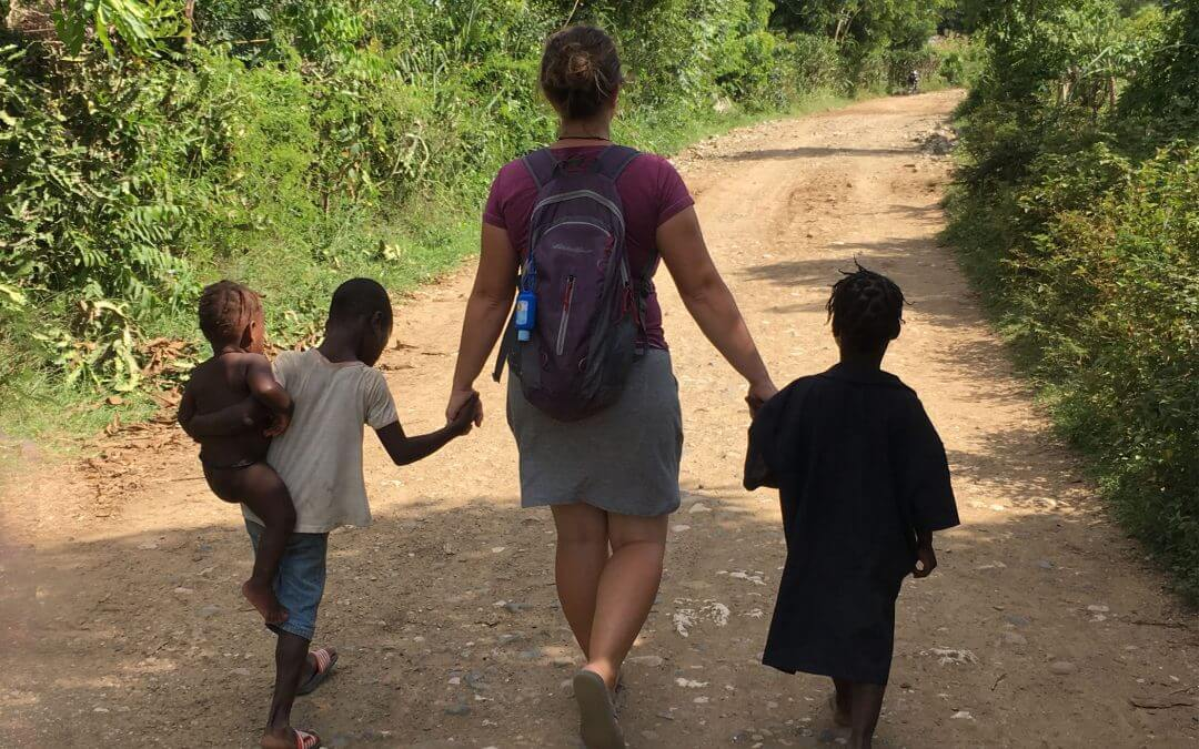 Liz holds the hands of children as they walk down a path.