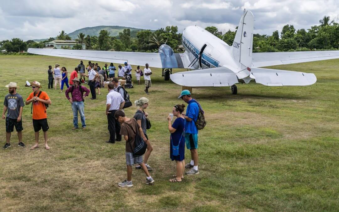 Volunteers and Haitians chat around a plane.