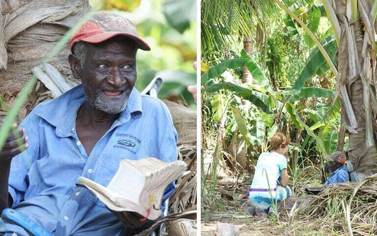 An elderly man reads a bible under a tree.