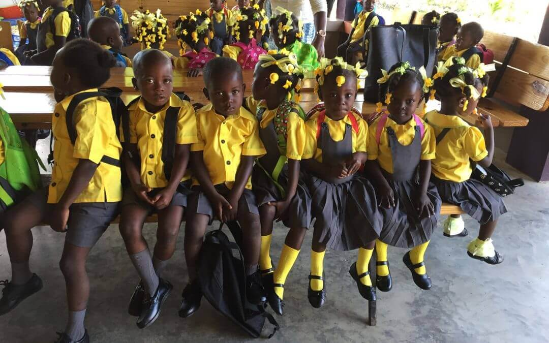 School children dressed in yellow and black uniforms sit on a bench.
