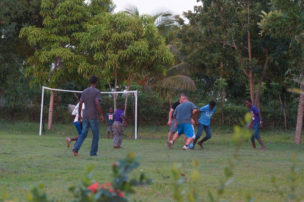 Volunteers play soccer with the neighbors.