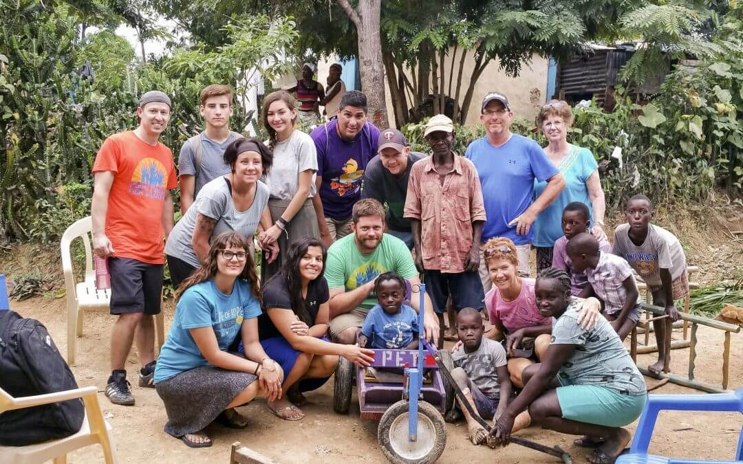 A group of volunteers and community members pose with a PET cart.