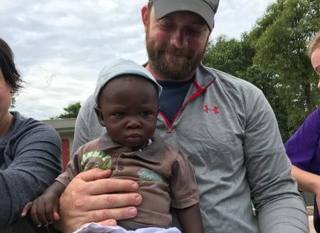 A volunteer holds a baby boy with a hat on.