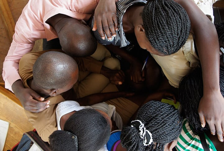 A group of haitians pray together in a huddle.